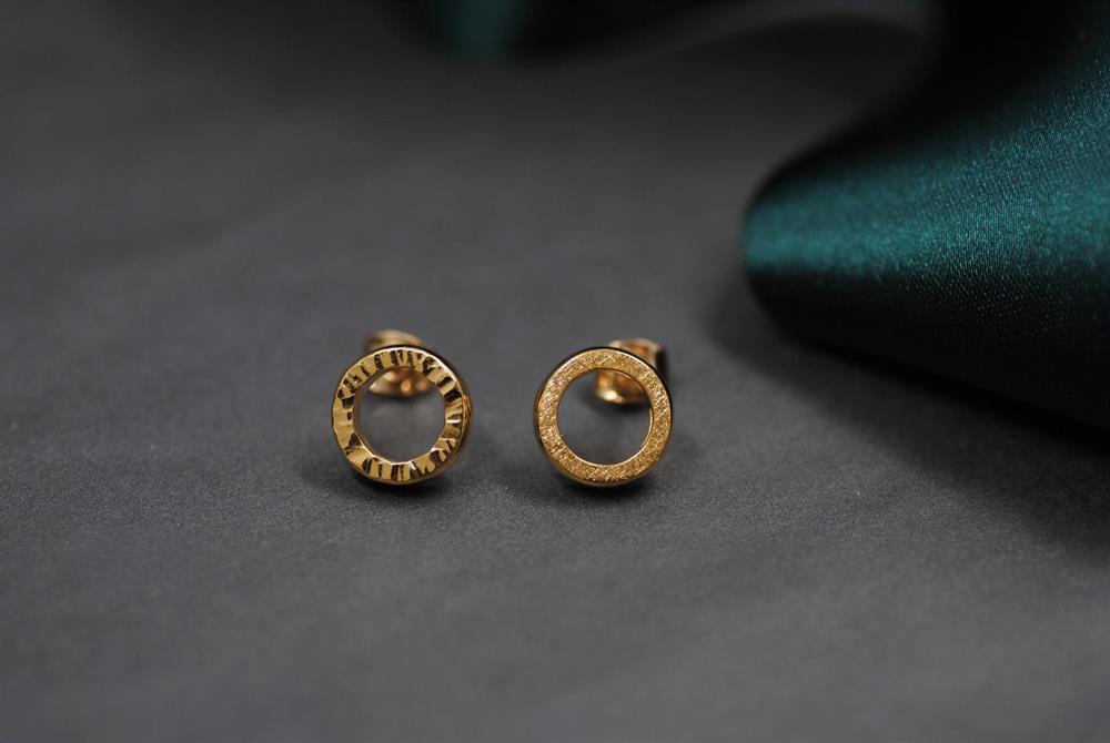 Örhängen tillverkade av en slät guldring. Exempel på ytor som gör ditt smycke personligare.