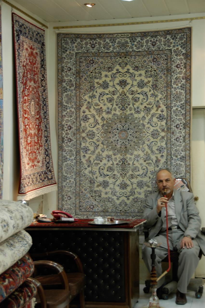 Handler av orientalske tepper i Isfahans basar venter på kunder