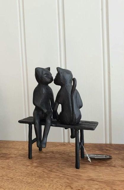 Smidesfigur katter på bänk