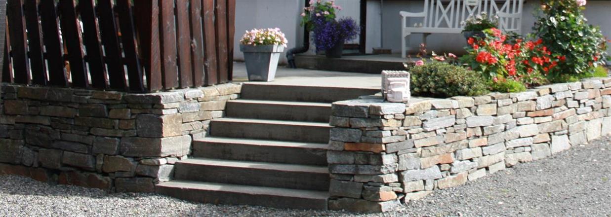 Natursteinsmur med bed rundt trapp