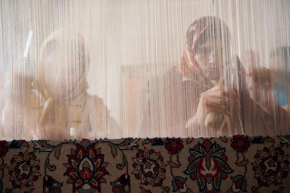 To kvinner knytter et orientalsk teppe i en landsby i Iran
