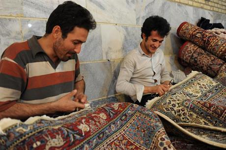 Reparatører i gang med å restaurere persiske tepper.