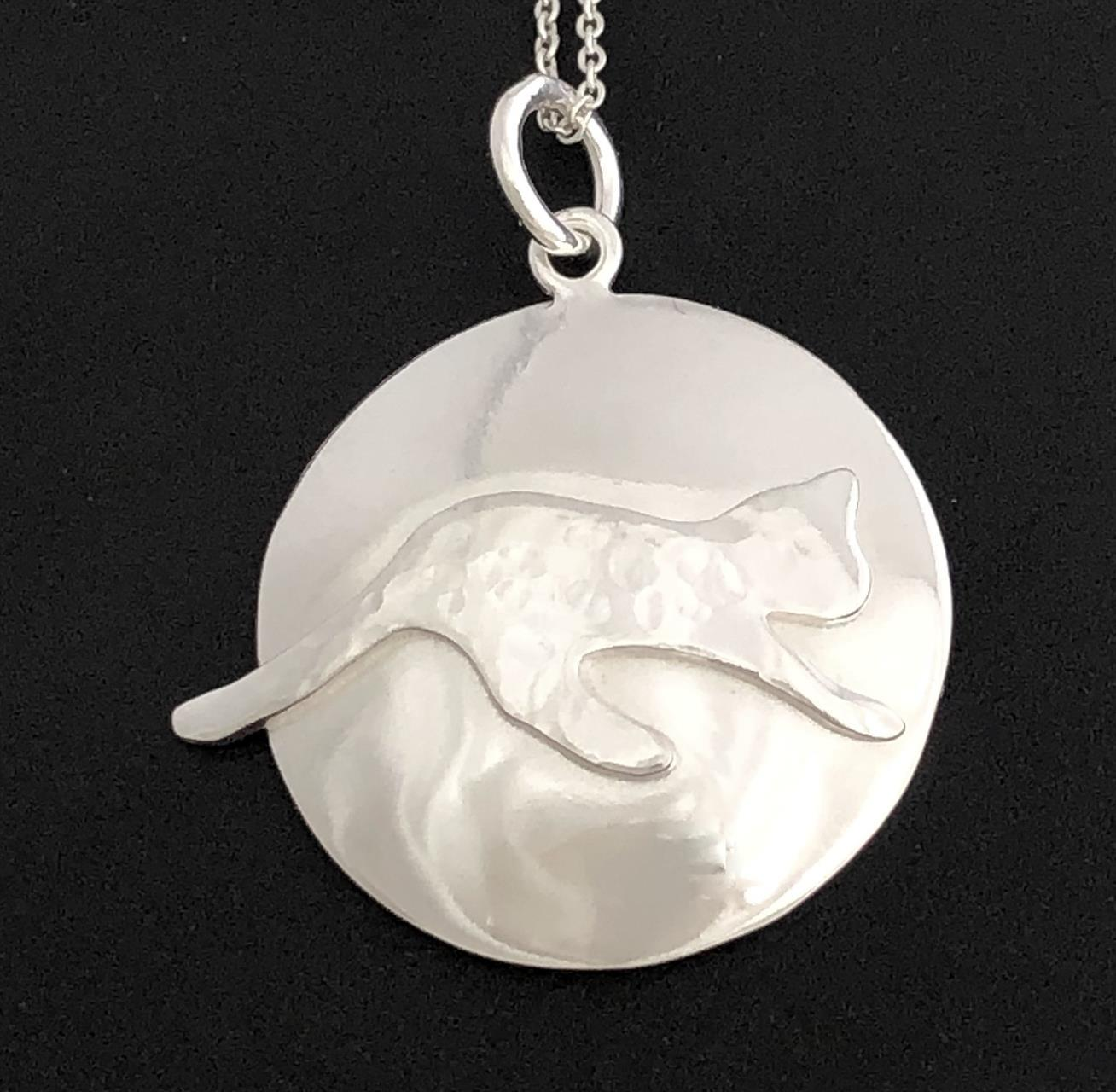 Prickig blank katt på runt blankt halssmycke i silver.