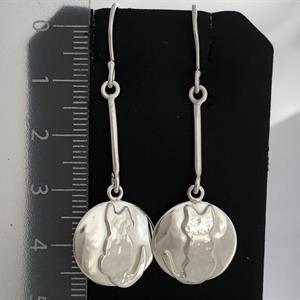 Silverörhängen med prickaiga katter på blank botten.