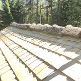 Avslut med stickespån mot taknock. Taket ska ströas och läktas och sedan få tillbaka tegelpannorna igen.
