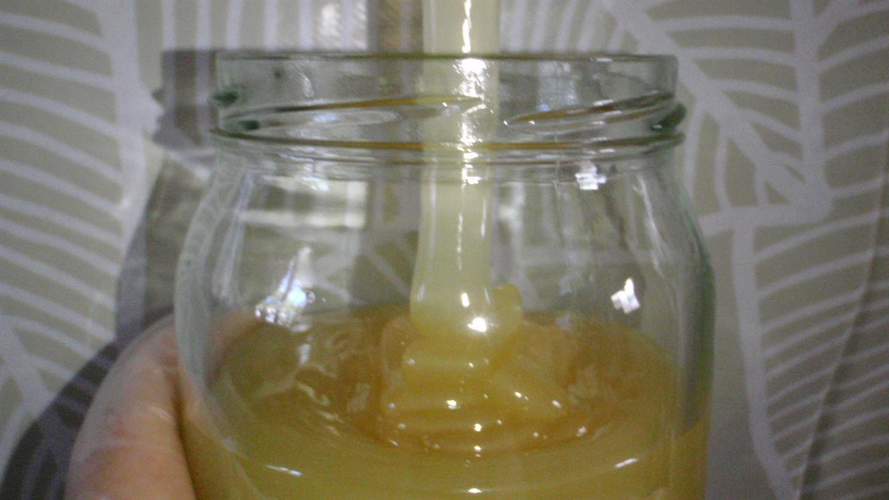 Upptappning av honung på burk innan den stelnar till.