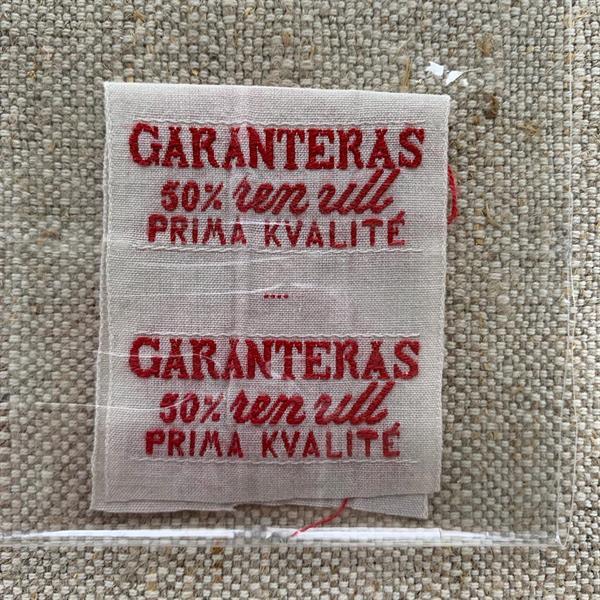 """Garanteras 50%"" tygetikett röd"
