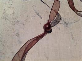 Brunt organzaband med bruna pärlor.