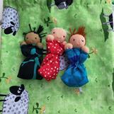Tre orosdockor i grön påse med får
