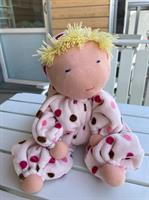 Stor rosa kramdocka med luva och blond lugg