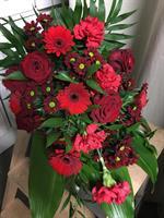 Begravningsbukett med blommor i röda färger