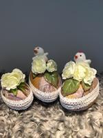 Tre dekorerade påskägg med vita sidenblommor